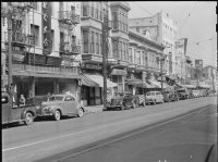 Street scene in black and white with store fronts of buildings, cars, Japanese lettering on one building